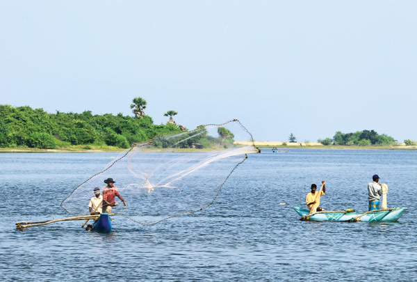 Fishermen casting nets by the Bar Road where the lagoon meets the sea